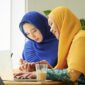 Female muslim students working on project together at cafe table