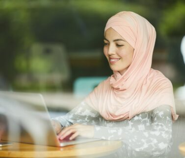 Pretty positive young woman in pink hijab answering e-mails on laptop
