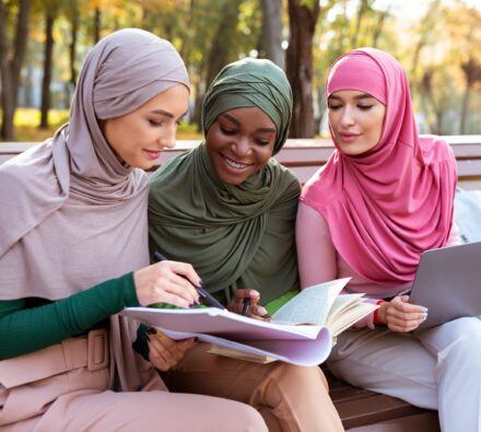 Three Muslim Students Women Learning Together Reading Books And Using Computer Sitting On Bench In University Campus Park Outdoors. Education For Modern Arabic Ladies, Online Study Concept