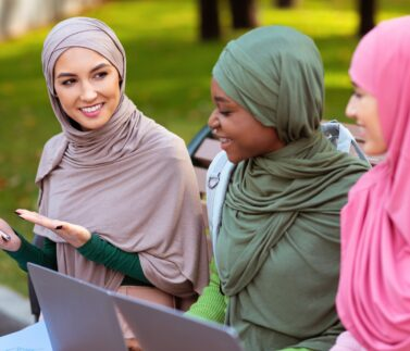 Modern Muslim Student Lady Recommending Smartphone Mobile Application To Friends Sitting On Bench Learning With Laptop Computers In Park Outdoors. Educational Application For Phone. Selective Focus